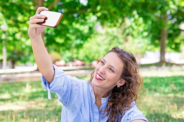陽気な若い女性がスマートフォンでselfieのポーズ 無料写真
