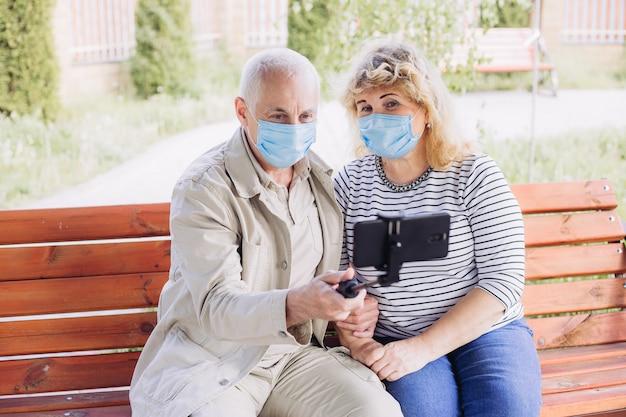 医療マスクを着用し、外でselfieを作る愛の美しいシニアカップル Premium写真