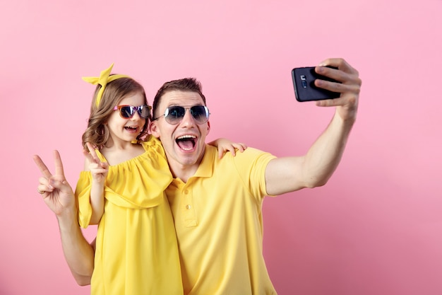 パパと小さな娘がスマートフォンでselfieを行う Premium写真