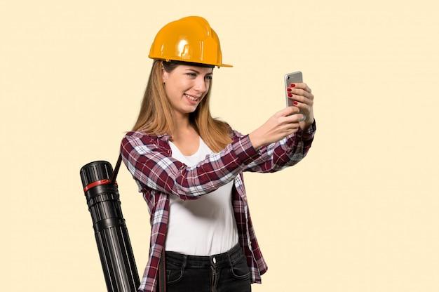 孤立した黄色の上のselfieを作る建築家女性 Premium写真
