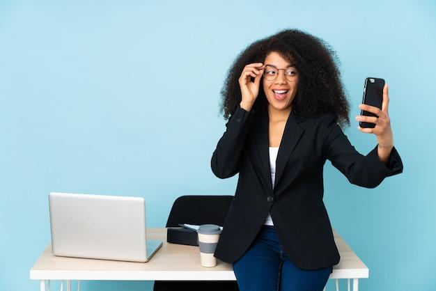 Selfieを作る彼女の職場で働くビジネスウーマン Premium写真