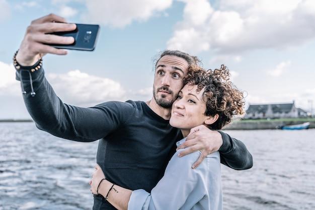 若いカップルは、ポートと海の焦点が合っていないselfieを作るを採用 Premium写真