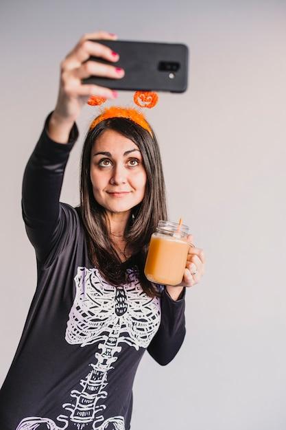 Молодая красивая женщина, пить апельсиновый сок и принимая selfie с мобильного телефона. одет в черно-белый костюм скелета. концепция хэллоуин в помещении Premium Фотографии
