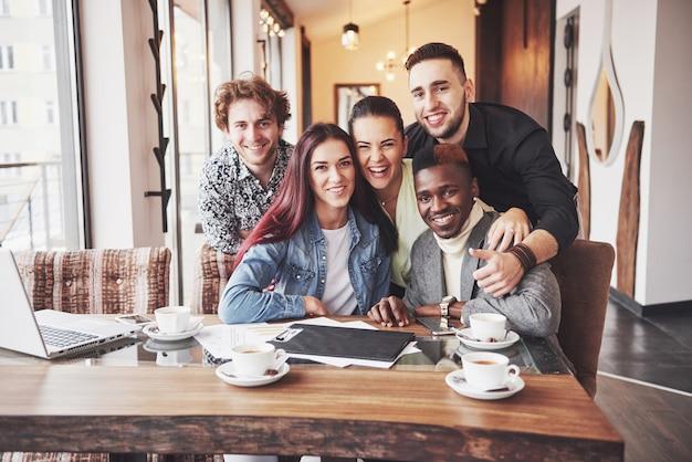 多民族の人々が携帯電話でselfieを取ってカフェで楽しんで Premium写真