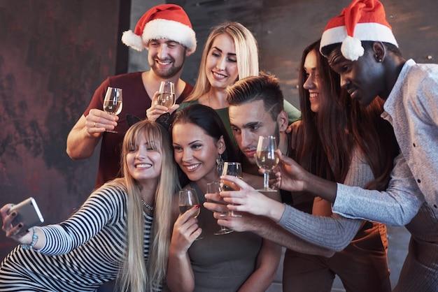 新年会でselfieをしている美しい若い人々、親友の女の子と男の子が一緒に楽しんで、感情的なライフスタイルの人々のポーズをグループ化します。帽子サンタとシャンパングラスを手に Premium写真