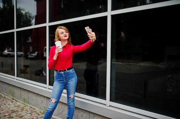 赤いブラウスと携帯電話でselfieを取り、巨大なショッピングモールの外のコーヒーカップを保持しているカジュアルなジーンズで美しい女性の肖像画。 Premium写真