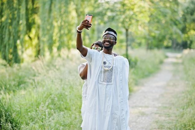 Счастливая жизнерадостная пара чёрного африканца в влюбленности делая selfie на их телефоне Premium Фотографии