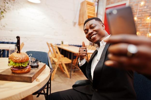 レストランに座っているとおいしいダブルバーガーに対してselfieを作って親指を現して黒のスーツで立派な若い男 Premium写真