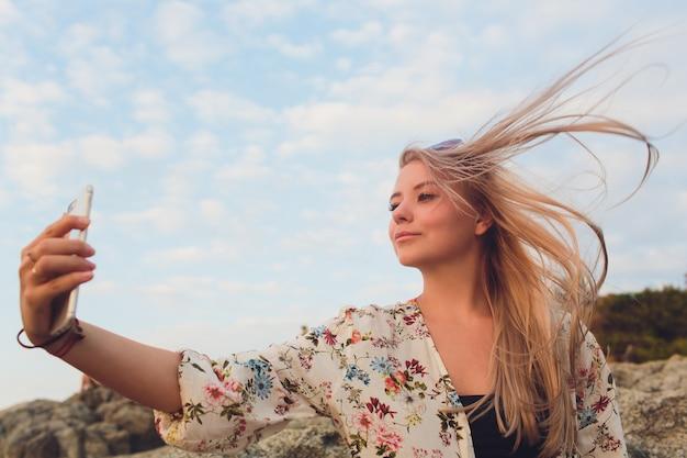 ビーチでselfieを作る幸せな金髪女の画像を閉じます。 Premium写真