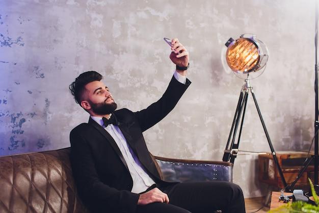 Selfieを取ってエレガントな黒のスーツでハンサムなスタイリッシュな男 Premium写真
