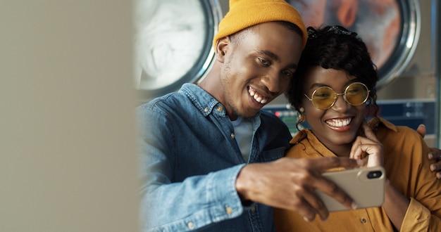愛を抱いて、ランドリーサービスでselfie写真を撮りながらスマートフォンのカメラに笑顔で幸せなアフリカ系アメリカ人カップル。陽気な若い男と女が洗濯機で電話で写真を作る。 Premium写真