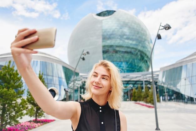黒で笑顔の金髪少女の肖像画は、ガラスビジネスの建物の背景に携帯電話でselfie写真になります Premium写真