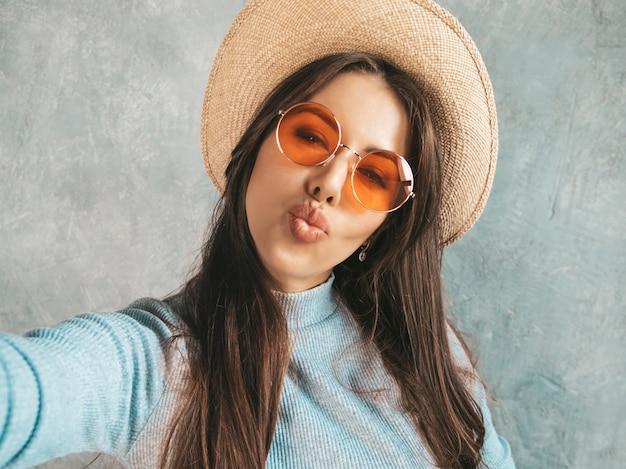 写真selfieを取り、モダンな服と帽子を着て陽気な若い女性の肖像画。 無料写真