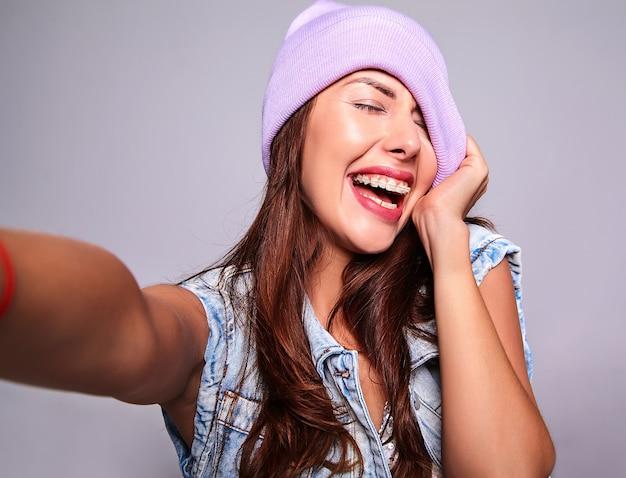 グレーに分離された携帯電話でselfie写真を作る紫色のビーニーでメイクなしのカジュアルな夏ジーンズ服で美しい笑顔かわいいブルネットの女性モデルの肖像画 無料写真