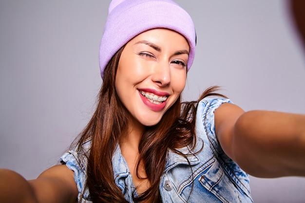 グレーに分離された携帯電話でselfie写真を作る紫色のビーニーでメイクなしのカジュアルな夏のジーンズ服でかわいいブルネット美人モデルの肖像画 無料写真