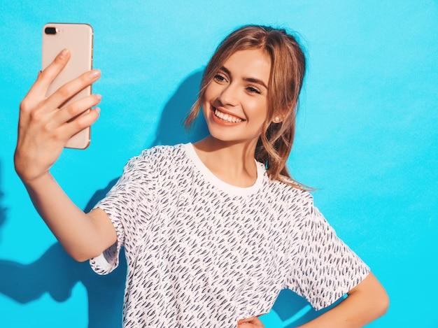 写真selfieを撮る陽気な若い女性の肖像画。スマートフォンのカメラを保持している美しい少女。スタジオで青い壁に近いポーズ笑顔モデル 無料写真