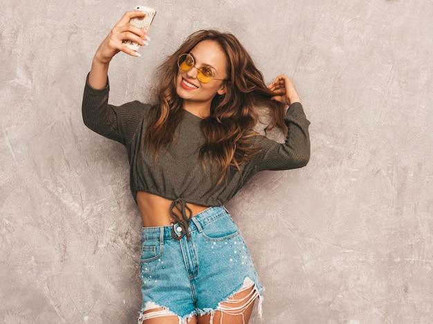 インスピレーションと写真selfieを取り、モダンな服を着て陽気な若い女性の肖像画。スマートフォンのカメラを保持している女の子。モデルのポーズ 無料写真