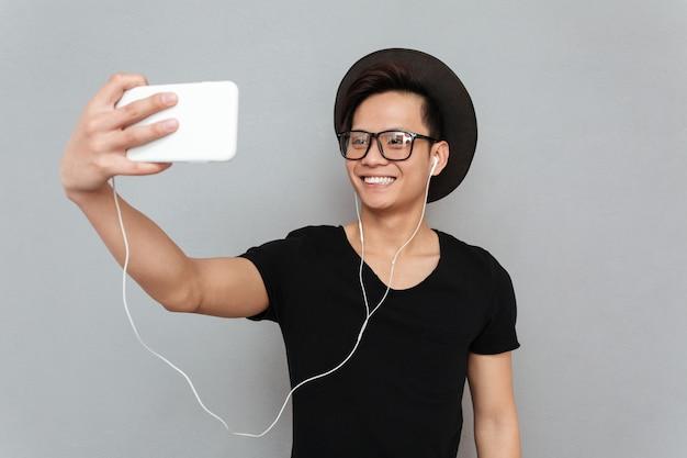 音楽を聴く若いアジア人の笑顔とselfieを作る 無料写真