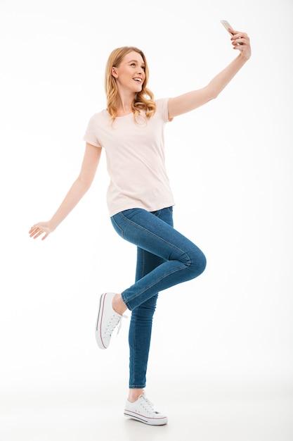 幸せな若い女性は、携帯電話でselfieを取ります。 無料写真