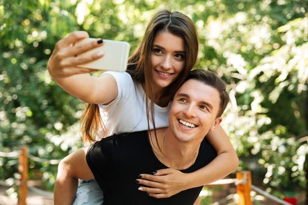 Selfieを作る愛の笑顔の魅力的なカップルの肖像画 無料写真