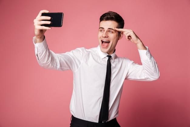 Счастливый молодой бизнесмен сделать selfie по мобильному телефону. Бесплатные Фотографии