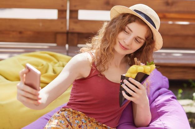 Selfieを取って、片手でスマートフォンを保持している、食べ物を持っている、カラフルなビーンズバッグに座って、外の木製のフェンスを越えてポーズ笑顔のリラックスした若い女の子の肖像画を閉じます。残り時間の概念。 Premium写真