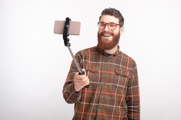 笑みを浮かべて男は白い背景の上のselfieを作っています。 Premium写真