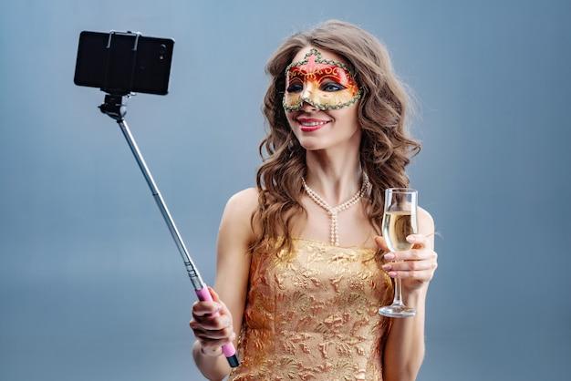 カーニバルマスクと上げられたガラスと黄金のドレスで微笑んでいるブルネットの少女の写真は、携帯電話でselfieを作る Premium写真