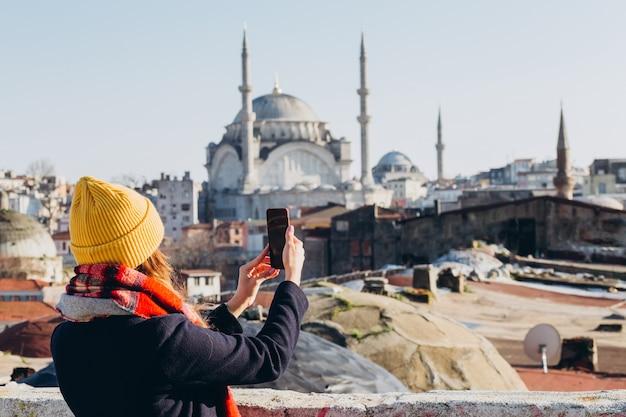 ブロンドの女性は、トルコ、イスタンブールのグランドバザールの屋根の上の電話で写真を作成します。黄色い帽子の少女は、晴れた秋の日にselfieを取ります。旅行者の女の子は、冬のイスタンブールを歩きます。 Premium写真