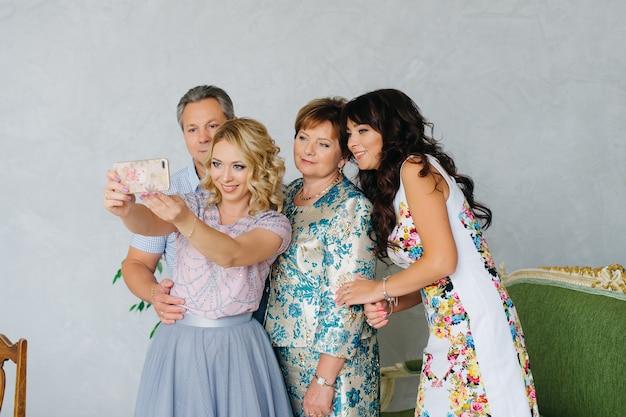 家族、世代、人々のコンセプト-幸せな家族が自宅でスマートフォンでselfieを取って Premium写真
