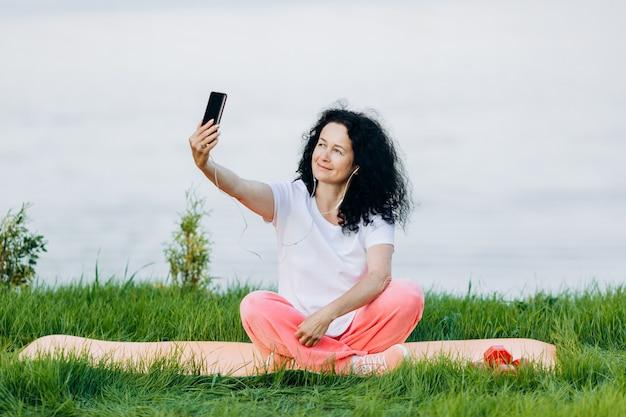 Счастливая старшая женщина сидя на циновке йоги напольной в наушнике и фотографирует selfie. Premium Фотографии