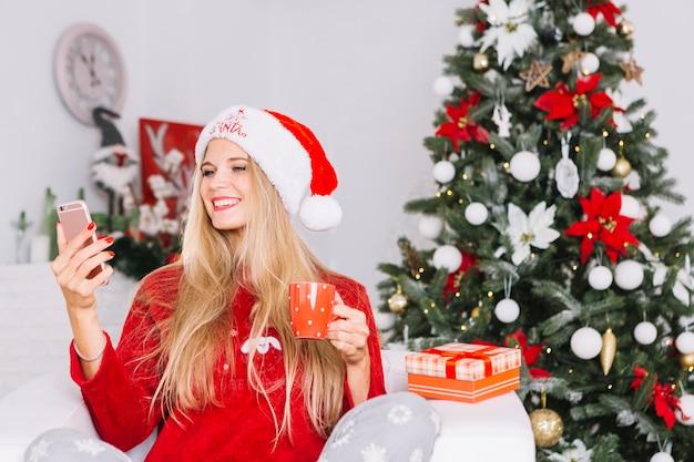 クリスマスツリーの背景にselfieを取っている女性 無料写真