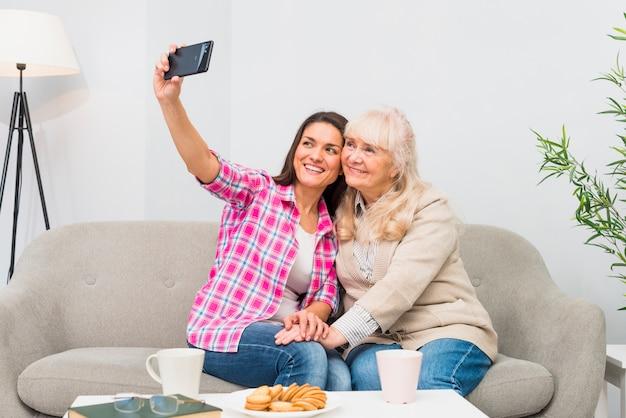 幸せな母と娘のテーブルの上の朝食付き携帯電話にselfieを取って 無料写真