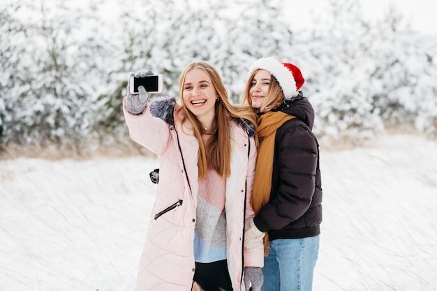 冬の森でselfieを取ってサンタ帽子で幸せな女性 無料写真