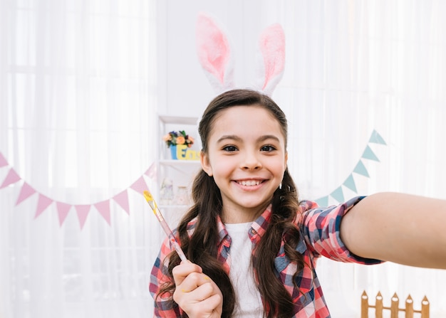 Selfieを取ってバニーの耳を着ている娘の笑顔の肖像画 無料写真