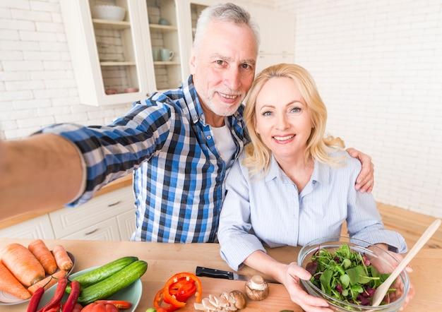 台所でサラダを準備しながらselfieを取って幸せな先輩カップルの肖像画 無料写真