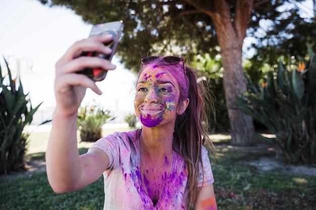 携帯電話でselfieを取ってホーリー色で覆われている若い女性のクローズアップ 無料写真