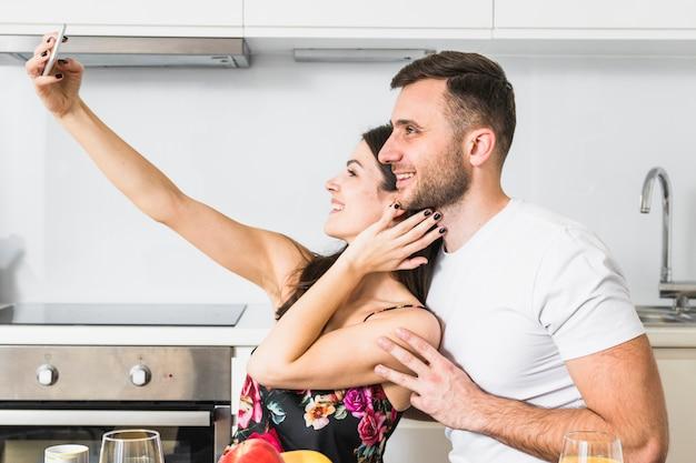 台所で携帯電話でselfieを取って愛する若いカップル 無料写真