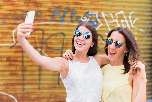 都市通りに立っている間selfieを取っている若い女性 無料写真