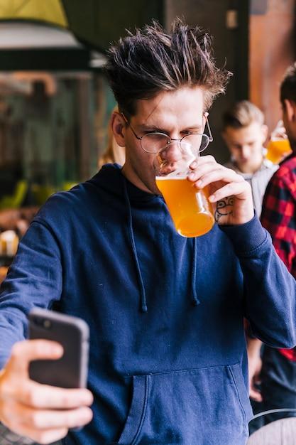 若い男がスマートフォンでselfieを取ってビールのグラスを飲む 無料写真