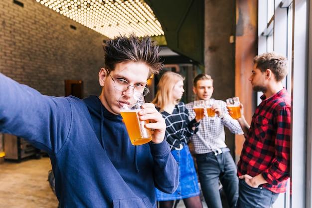 背景に立っている彼の友人とselfieを取ってビールのグラスを飲む若い男の肖像 無料写真