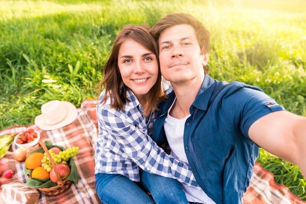 格子縞のガールフレンドとselfieを取っている若い男 無料写真