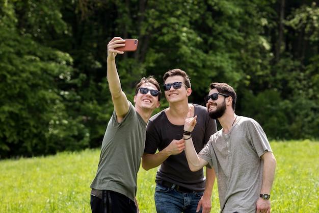 大人の男性が自然の中で電話でselfieを引き継ぐ 無料写真