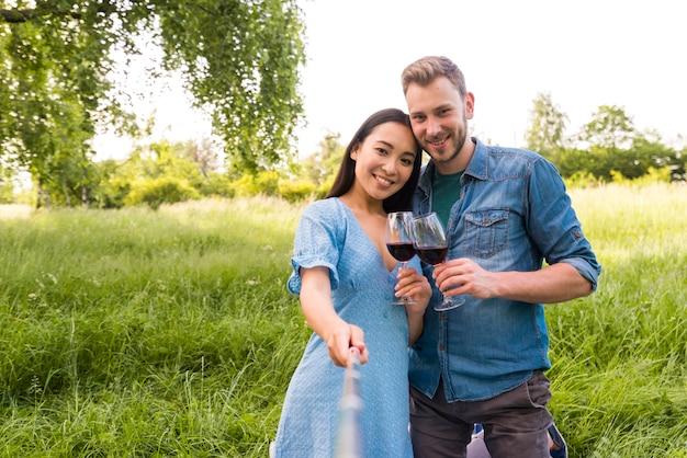 ワイングラスを持つselfieを取って多民族の若いカップル 無料写真