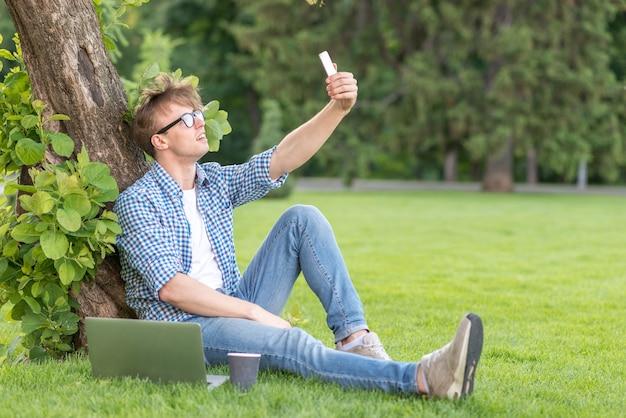 学校の男の子が公園でselfieを取って 無料写真