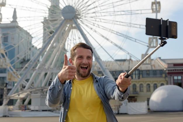 陽気な男の観覧車の前でselfieをしながらジェスチャー親指を表示 無料写真