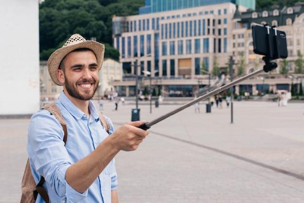 スマートフォンでselfieを取ってバックパックを運ぶ幸せな若い男の肖像 無料写真