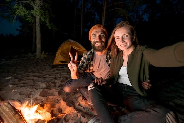 キャンプファイヤーで夜キャンプのカップルのselfie 無料写真