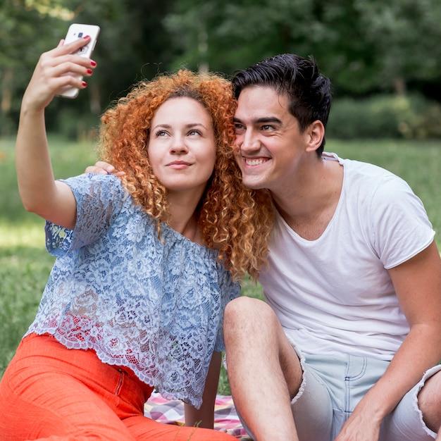 携帯電話で、selfieを取って愛のカップル 無料写真