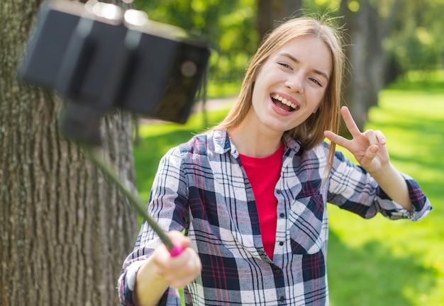 屋外で彼女の携帯電話でselfieを取っている女の子 無料写真